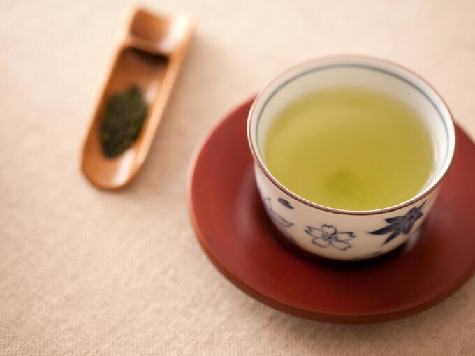 Tiny fibers of Sencha Fukamushi tea leaves infuse into the water. The brewed infusion color is green and cloudy.